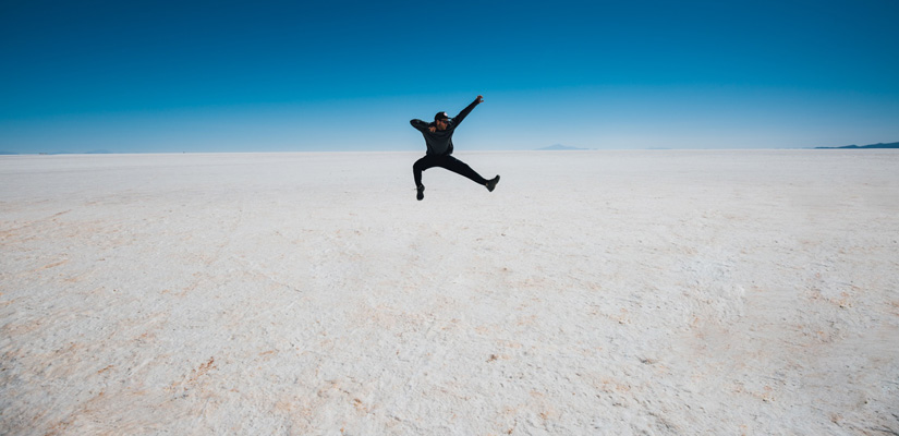 boy jumping in uyuni salt flats