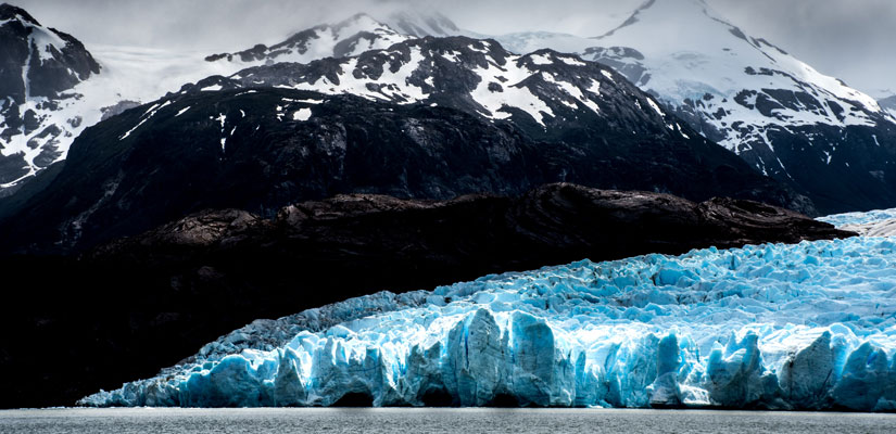 grey glacier with snowy mountain in patagonia