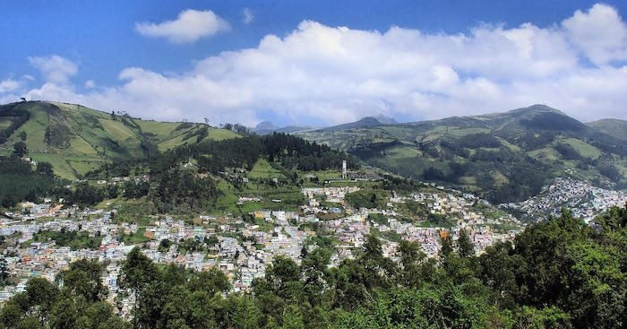 The city of Quito seen from far between volcanoes